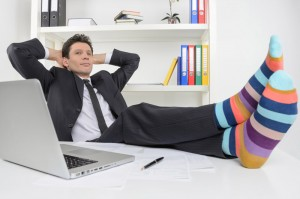 Businessman in funky socks. Confident businessman holding his le