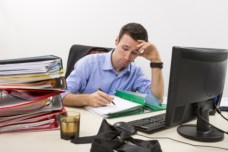 Stressed businessman filling paper documents in front of his computer surrounded by huge piles of documents.