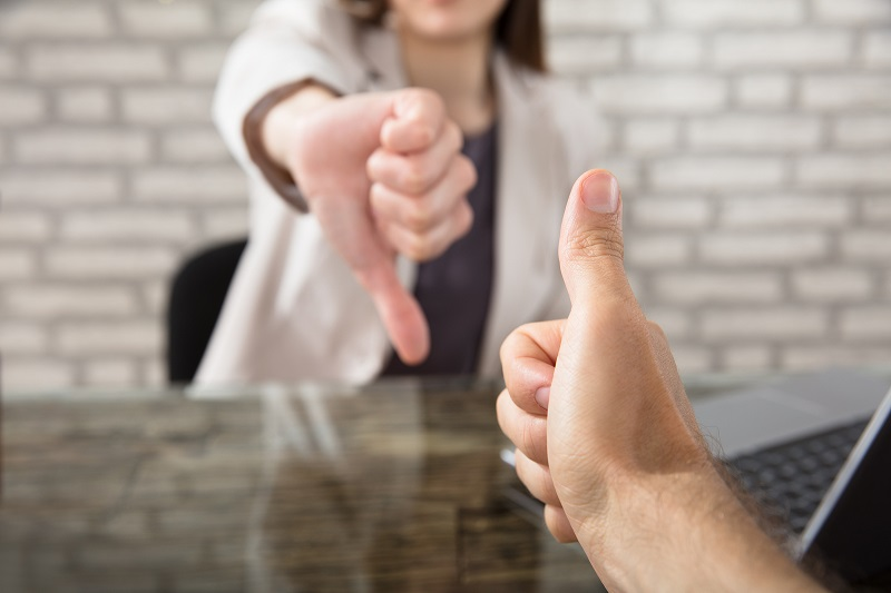 Business people showing thumbs up and down
